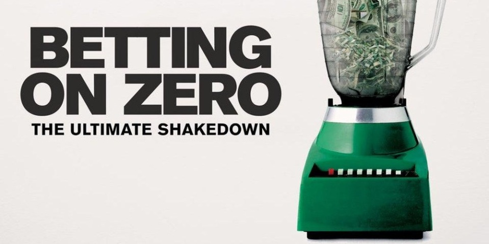 "Image Description: A green blender full of cash on an off-white background. To the side in large black letters is ""Betting on Zero"". Underneath in smaller letters is ""The Ultimate Shakedown"""